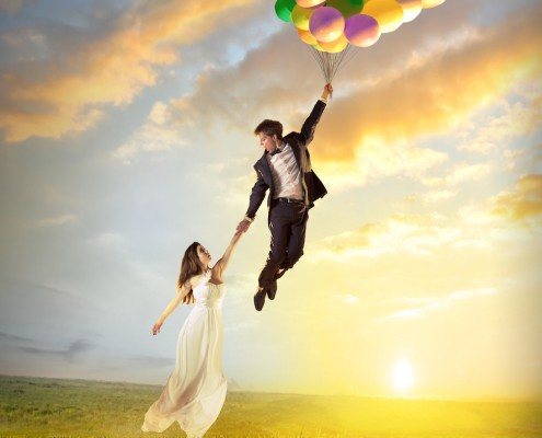Happy birthday woman against the sky with rainbow-colored air balloons in hands. sunny and positive